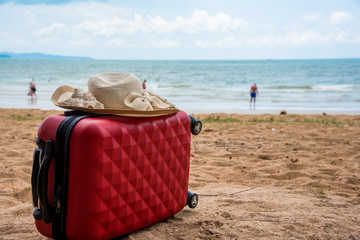 Red luggage and hat on the beach with blue sky