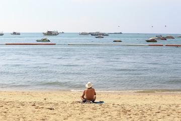 Old man sunbathe at the beach, Pattaya Thailand, as background