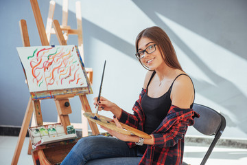 Creative pensive painter girl paints a colorful picture on canvas with oil colors in workshop
