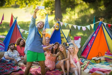 Man taking a selfie with friends at campsite