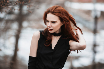 Portrait of glamorous girl with long red hair in black clothes. Woman in black dress and long black gloves posing on a background of winter, autumn nature. Female street style. Beautiful elegant model