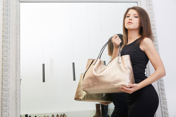 young beautiful woman choosing new bag in a luxury store