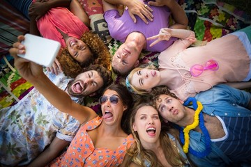 Group of friends lying in a circle and taking a selfie