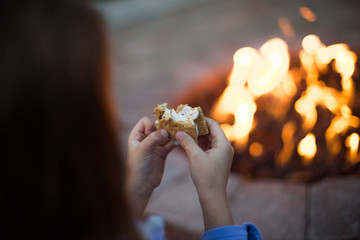 Close-up of girl's hand eating a biscuit by campfire
