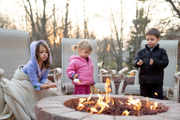 Three children around an open fire