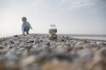 Boy collecting pebbles on beach