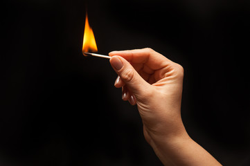 Woman hand holding lighted match, on black background.
