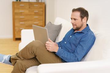 mann liest zuhause am laptop