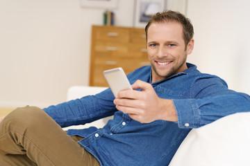 glücklicher mann sitzt entspannt auf dem sofa und hält sein mobiltelefon in der hand