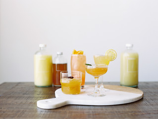 Row of citrus fruit cocktails and ingredients, close up
