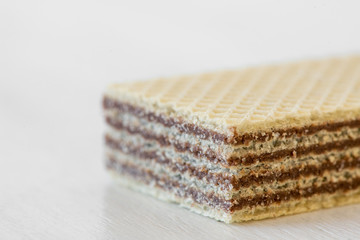 Closeup of a waffle with chocolate cream isolated on white background - selective focus, copy space