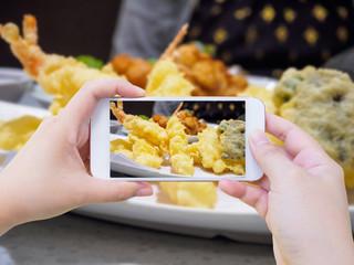 taking photo of shrimp tempura on white plate with smartphone