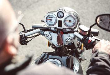 Back view of senior man steering motorcycle on the road