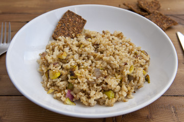 rice with vegetables dish in a wooden background with crackers and lemonade
