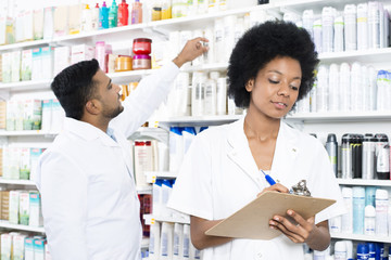 Chemist Writing On Clipboard While Colleague Arranging Products