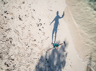 walking man in hat with hands asideand shade on african beach, top view, aerial photo