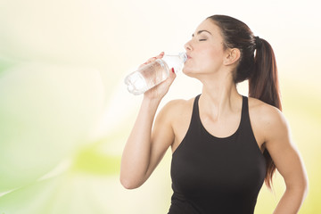 A young beautiful woman drinking from a bottle of water