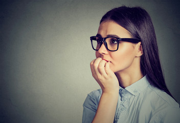 Hesitant woman biting fingernails craving for something or anxious