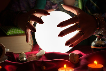 Crystal ball and hands of gypsy fortune teller woman above it