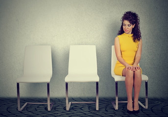 Young woman sitting on a chair waiting for job interview