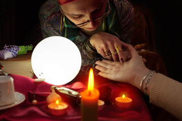 Fortune teller woman holding another woman hand for palm reading