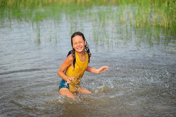 Little girl in a yellow bathing suit playing in the water