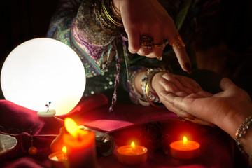 Woman fortune teller point with her finger on another woman palm