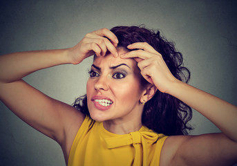 woman looking in a mirror squeezing acne or blackhead on her face