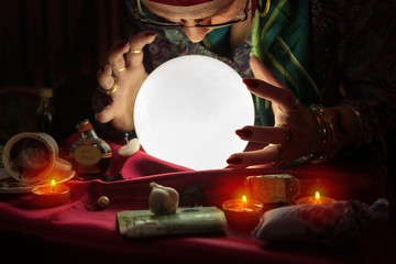 Gypsy woman looking at crystal ball and reading the future