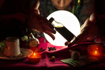 Woman fortune teller holding and showing bottle with potion