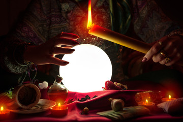 Woman fortune teller holding candle above crystal ball