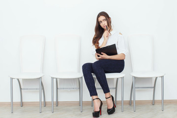 The girl sits on a chair and fills up the documents