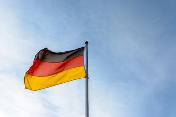 Deutschland Flagge - Fahne vor blauem Himmel