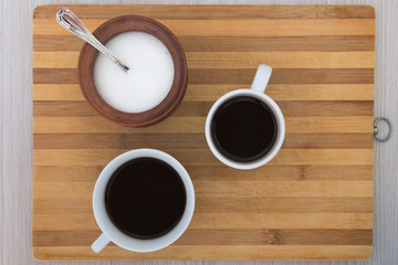 cup of coffee and a sugar bowl on a wooden table