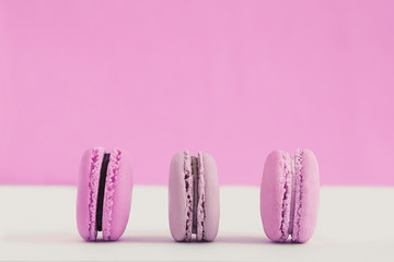 Assorted pink and purple french macaroons on a colored background. Copy space for text. Horizontal