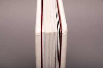 Detail of open photo book on grey background.  Luxury white leather photo book.