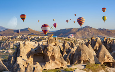 Hot air balloons fly in clear morning sky near Goreme, Kapadokya, Turkey