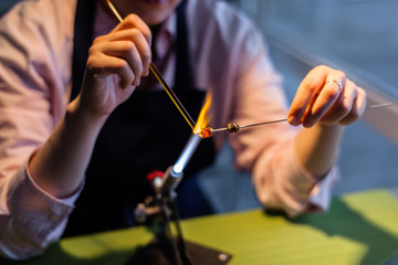 Lampworking - artistic treatment of glass in the flame. Woman master work gas. Burner glows (focus on the tools).