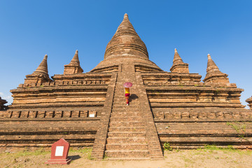 Bagan, Mandalay region, Myanmar (Burma). Woman walking on the steps of a stupa. MR.