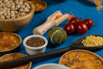 Bowls and spoons of various legumes on wooden table