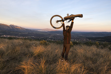 Smiling sportsman cyclist raising the mountain bike above his head with success on top of the hill at sunset