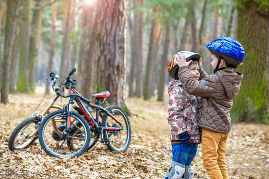 Two little kids boys, best friends in autumn forest. Older brother helping younger child to put his bike helmet. Happy siblings with bicycles.