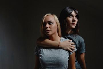 Two pretty woman in dark room