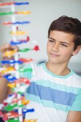 Attentive schoolboy experimenting molecule model in laboratory