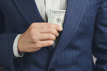 Business man put bundle with hundred dollars into jacket pocket, bribery concept.