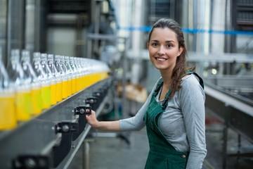 Fototapeta Female factory worker standing near production line obraz