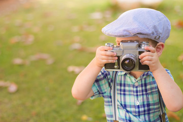 Little boy with an old camera shooting outdoor. using a vintage retro film cam. summer field.