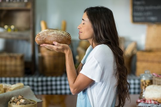 Smiling woman smelling a round loaf of bread at counter