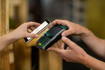 Woman making a payment by using NFC technology in the grocery store