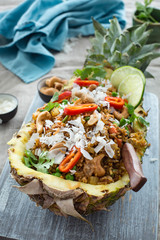 Pineapple fried rice served in a pineapple half. Traditional Thai dish.